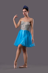 Front view of graceful ballerina looking at camera in studio