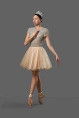 Graceful ballerina wearing beige dress posing in studio