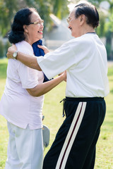An elderly man using towel to wipe the sweat from his wife's face after exercising