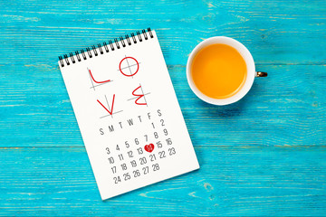 LOVE text with math charts in notepad over wooden turquoise planks, february 2019 month calendar