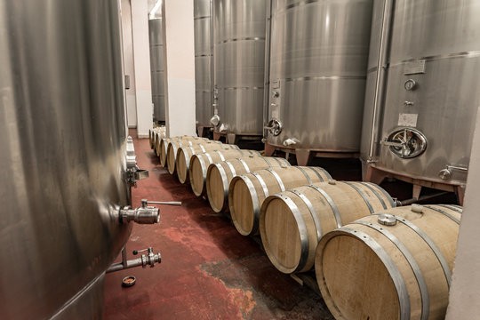 Interior of a winery making wine in oak barrels and aluminium tanks