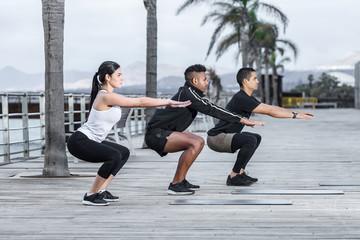 Athletes squatting on embankment