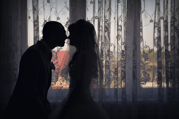 silhouette of bride and groom face to face. A man kisses a woman. Valentine's day
