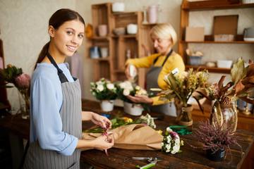 Obraz Portrait of smiling female florist cutting flower stems while arranging bouquets in flower shop, copy space - fototapety do salonu