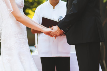 The midsection of young couple hold hand at wedding ceremony