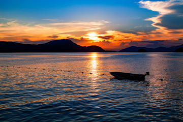 Small fishing boat in the sea sunset scenery, Beautiful Landscape and light of nature in evening with beautiful colors Clouds and sky