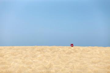Red alarm clock on tropical sea beach blue sky background