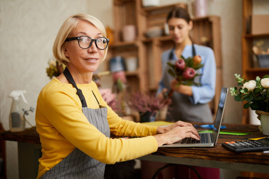 Side view portrait of mature female small business owner using laptop and looking at camera in flower shop, copy space