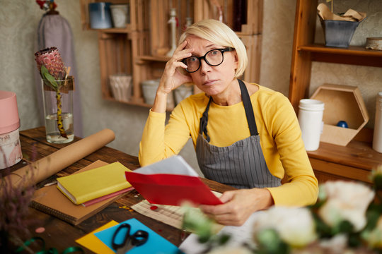 Portrait of female business owner holding red envelope while doing accounting in flower shop, copy space