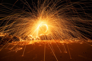 Swing fire Swirl steel wool light photography over the stone with reflex in the water long exposure speed motion style