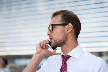 Businessman talking on his business smartphone. Business call and b2b concept, handsome man