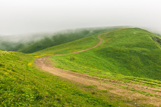 Tranquil highland scenery with dirt winding country road on the green rolling hills on a foggy summer day. Countryside landscape at North Caucasus mountains. Karachay-Cherkessia, Russia