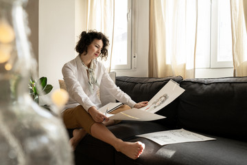 Woman drawing on papers on sofa in room
