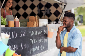 street sale and people concept - happy smiling male customer looking at billboard at food truck