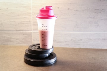Protein drink and dumbbells