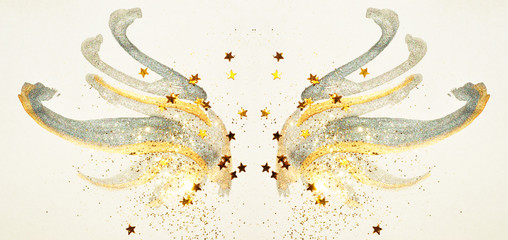 Glitter and glittering stars on abstract gold and black watercolor wings in vintage nostalgic colors.