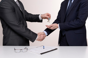 two businessmen shaking hands and giving keys