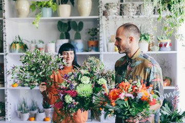 Man and woman carrying bouquets in flower shop.