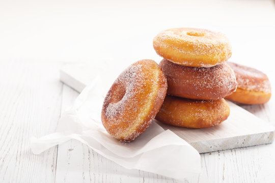 Donuts on white wooden table. Copy space