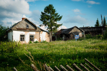 Abandoned houses in the village against the blue sky, broken roofs and fences