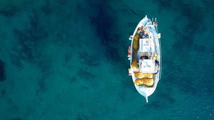 Aerial drone bird's eye view of small traditional fishing boat in port of Mykonos in sapphire clear waters, Cyclades, Greece