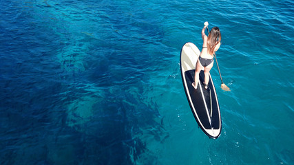 Aerial photo top view of unidentified fit woman on sup or stand up paddle surf board in tropical caribbean turquoise clear water beach