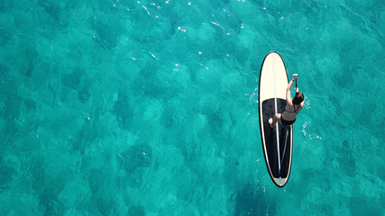Aerial top view photo of unidentified woman with her sup paddle board in coast of caribbean clear sandy beach