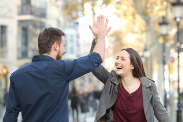 Excited friends giving high five in the street