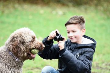 Junge fotografiert seinen Hund mit Ball im Mund