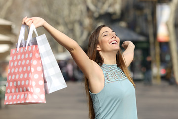 Happy shopper holding shopping bags in a street