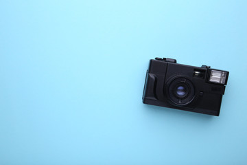 Vintage camera on blue background. Old photo camera on wooden background