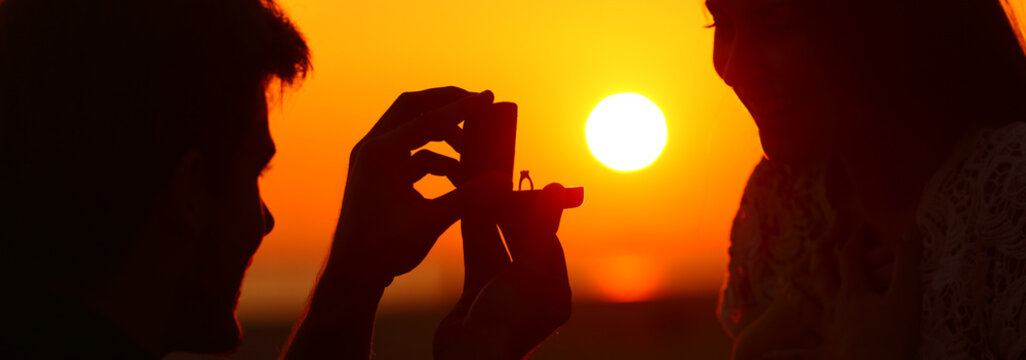 Banner of silhouette of marriage proposal at sunset