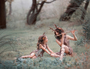 creative photo idea for mom and daughter, child and mother dressed as deer are sitting on the grass in the forest, a woman playing the flute, the girl following the melody carefully, art processing