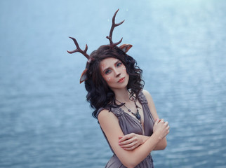 interesting photo of mother deer in front of lagle lake, characters of the fairy forest, image of a sad woman-faun near a large lake, unusual makeup, with homemade horns and ears on dark curly hair