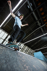 Happy active guy on skateboard standing on edge ready to descend along parkour racetrack in front of camera