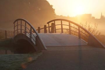 Wooden, steel bridge for pedestrians on a misty morning in a natural park at sunrise, November. Park Sonsbeek Arnhem, Netherlands.