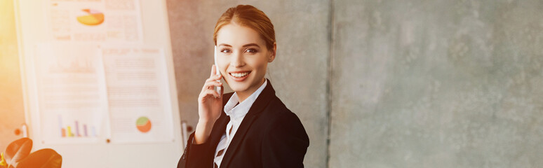 smiling businesswoman talking on smartphone and looking at camera in office