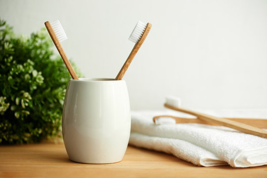 The bamboo toothbrushes in a gray glass with copy space in bathroom