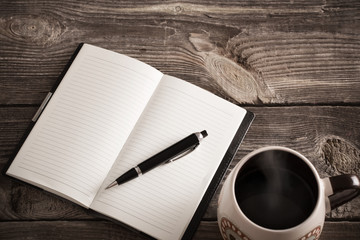 notebook with pen and coffee  on old  wooden table