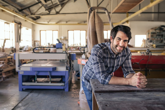 Woodworker smiling while leaning on a bench in his workshop