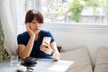 Asian woman sitting in cafe and waiting notification message on her smartphone.  Female watching her photo on cell telephone while relaxing in cafe during free time. Image.
