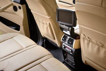 Interior in cream colors leather of prestige luxury modern car. Swivel display for back seats passenger