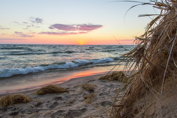 Michigan Sunset Beach. Gorgeous sunset over a sandy beach on the coast of Lake Michigan with dune grass in the foreground.