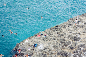 Acitrezza, Catania, Sicily, Italy – august 08, 2018: people bath in the sea near rocks of the Cyclops.