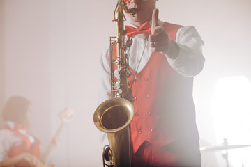 elegant guy in suit with saxophone showing thumbs up. close up cropped photo. best music. perfect tune