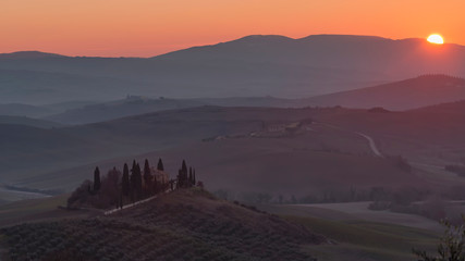 The sun rises behind the hills illuminating the Val d'Orcia countryside, Siena, Tuscany, Italy