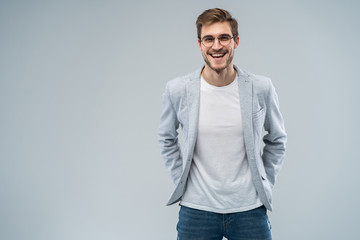 Portrait of attractive masculine fashionable modern stylish guy wearing blue blazer, jeans keeping hands in pockets isolated on gray background.