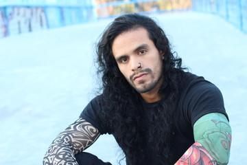 Tough looking hispanic man with long hair and tattoos