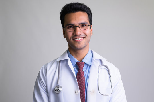 Portrait of happy young handsome Indian man doctor smiling