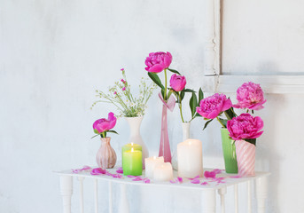 flowers in vases and candles on white background